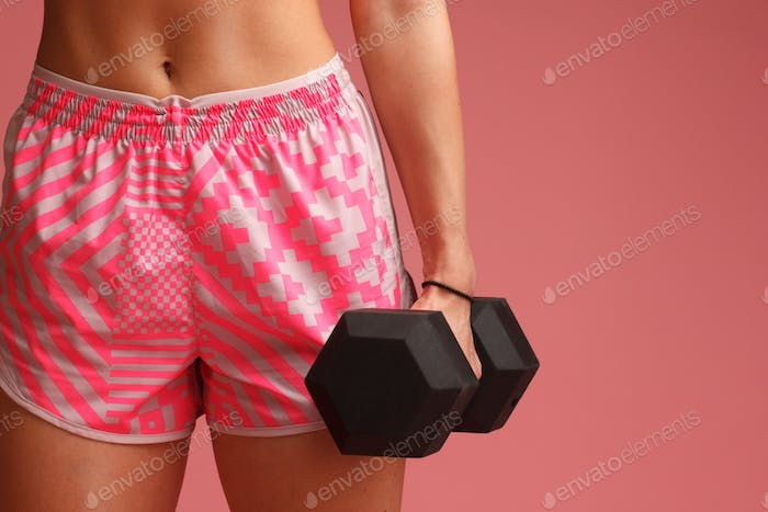 athletic sexy female in pink sportswear isolated on pink background