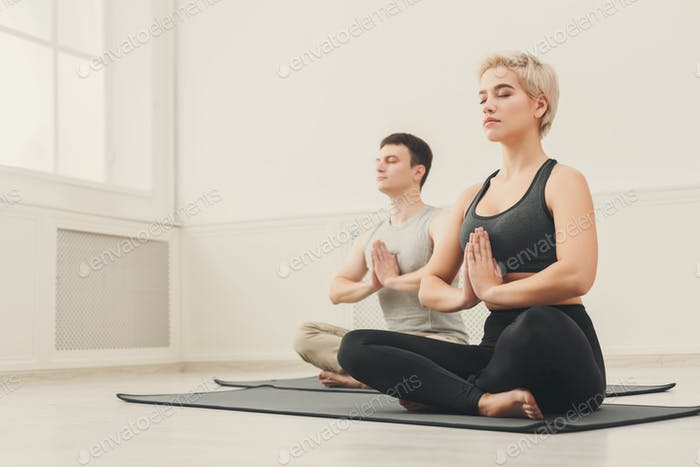 Young couple practicing yoga sitting in padmasana