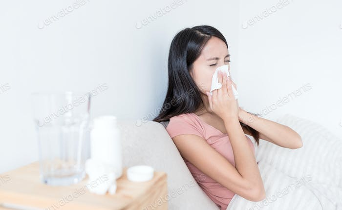 Женщина чихает на кровати