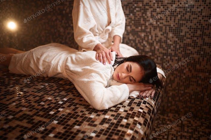 Weibliche Masseurin macht Massage Frau in der Sauna