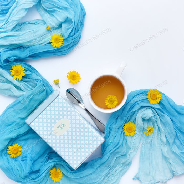 Cup of black tea with yellow daisy flowers and blue scarf on whi