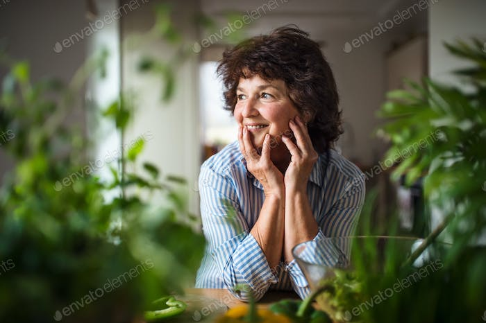 Senior woman preparing food in kitchen at home, relaxing