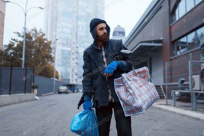Bearded tramp man with bag on city street