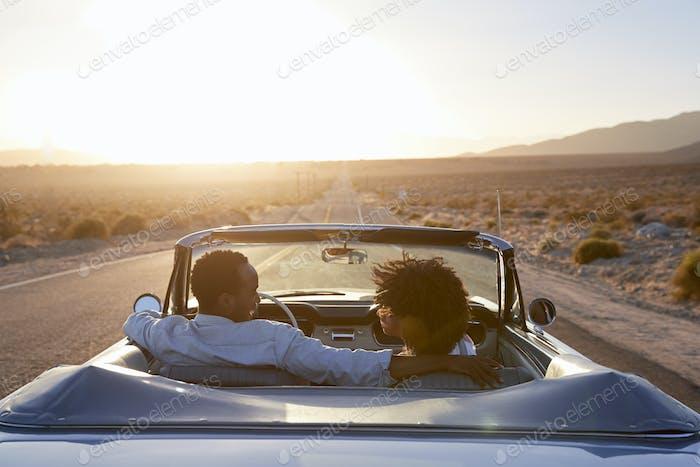 Vista trasera de pareja en viaje de Carretera conduciendo coche convertible clásico hacia el atardecer