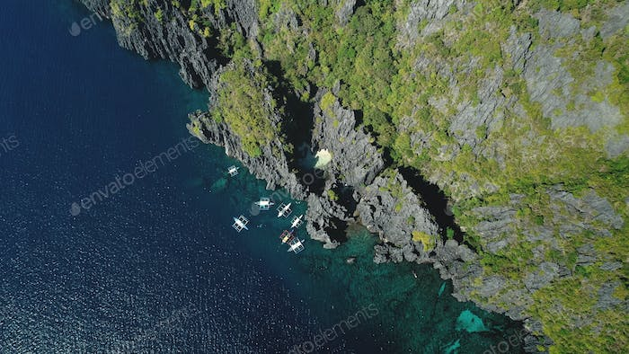 Passenger boat at cliff ocean shore at tranquil seascape aerial view. Majestic nature at rock island