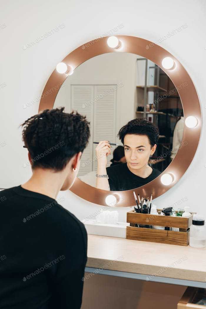 Attractive woman at the mirror in beauty studio