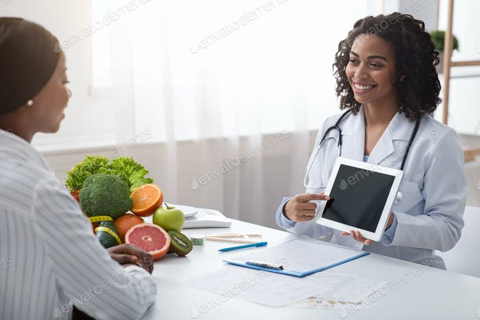 Female nutritionist using digital tablet in office, making patient's anamnesis