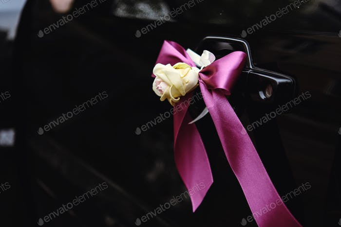 elegant luxury black car decorated with roses and purple ribbons for a wedding