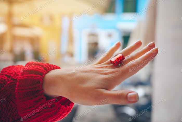 Female hand with a red ring