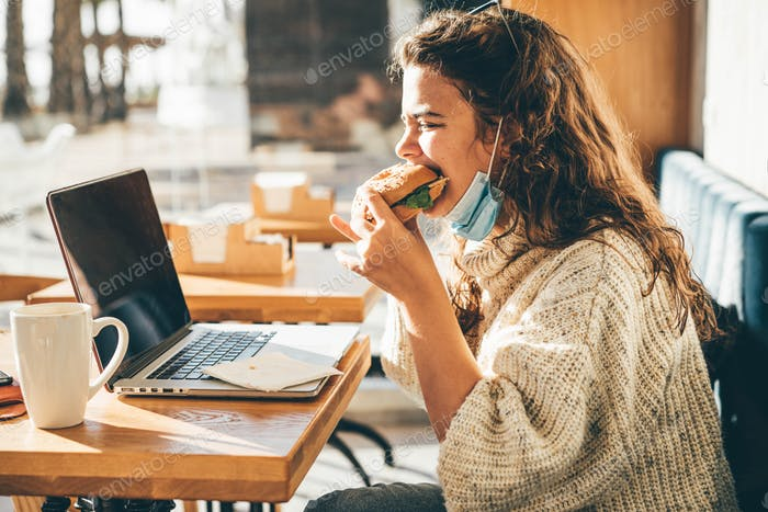 Woman with face mask eating sandwich and using laptop at the cafe.