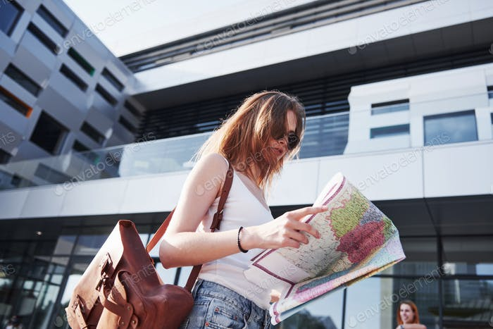Female tourist with map visiting a new city and is looking for a way to the hotel