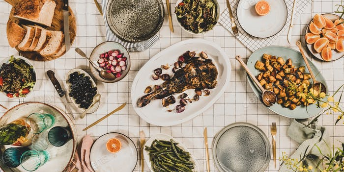 Flat-lay of meat, salads, snacks, lemonade and blooming mimosa branches