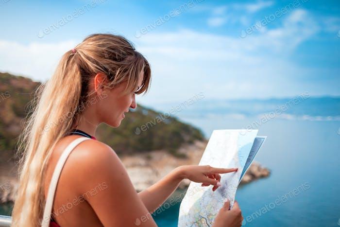 Glückliche junge Touristenfrau mit Landkarte am Ufer, Reise-Lifestyle