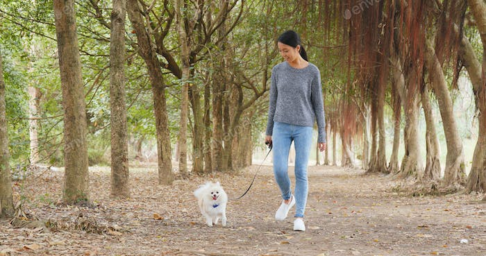 Woman walking with her dog in park