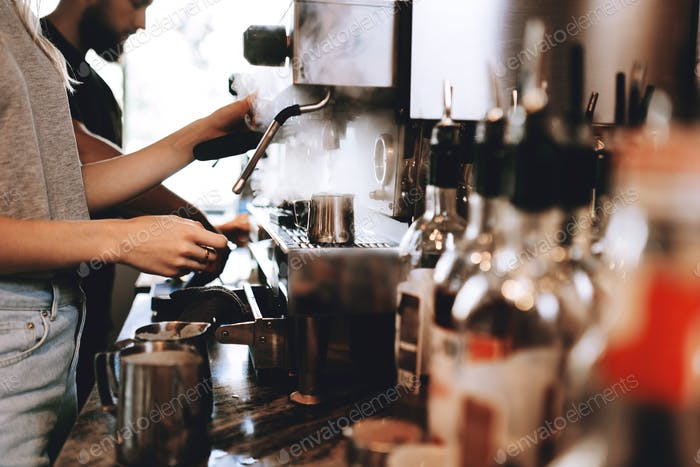 A modern expensive coffee machine is shown in work in modern cozy coffee shop
