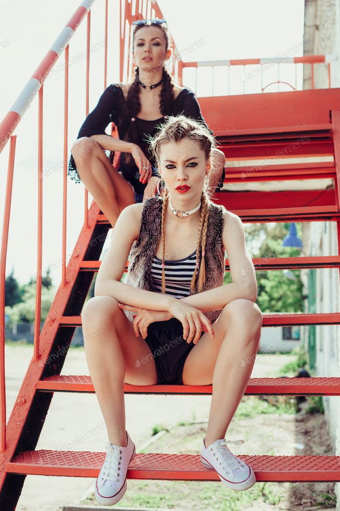 Two young cheeky girls sitting on stairs