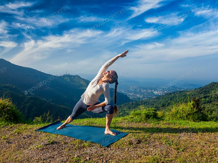 Woman practices yoga asana Utthita Parsvakonasana outdoors