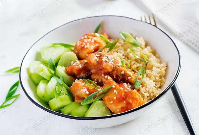 Fish fillet cooked in tomato sauce with bulgur and cucumber