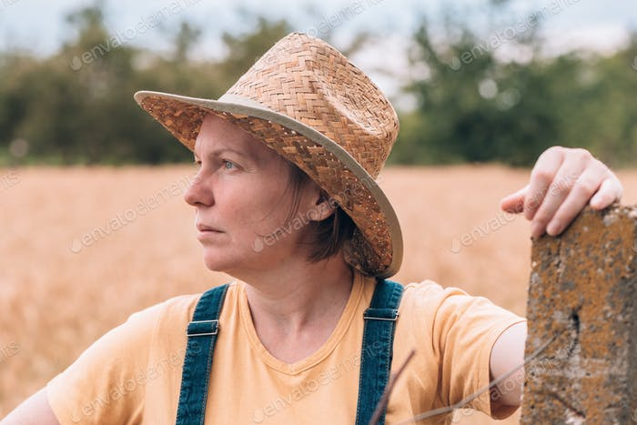 Female farmer posing in ripe barley field just before the harvest
