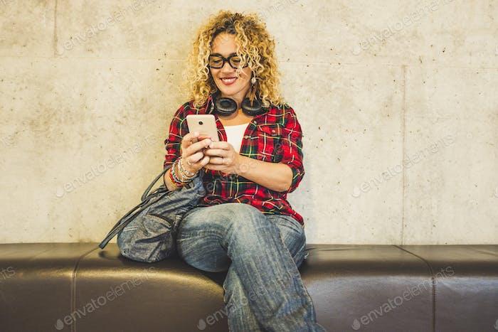 Schöne glückliche kaukasische Frau setzen sich auf ein Sofa