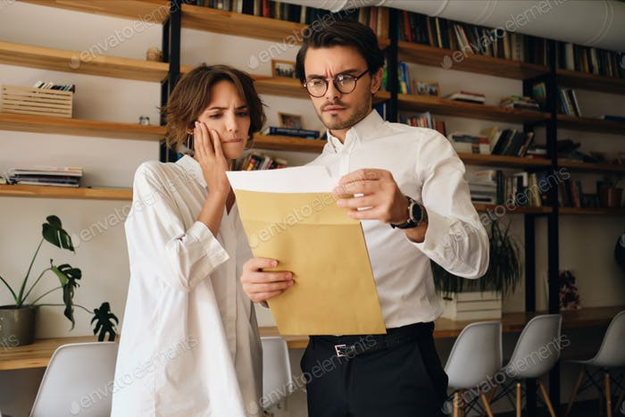 Young business colleagues thoughtfully reading envelope letter working together in modern office