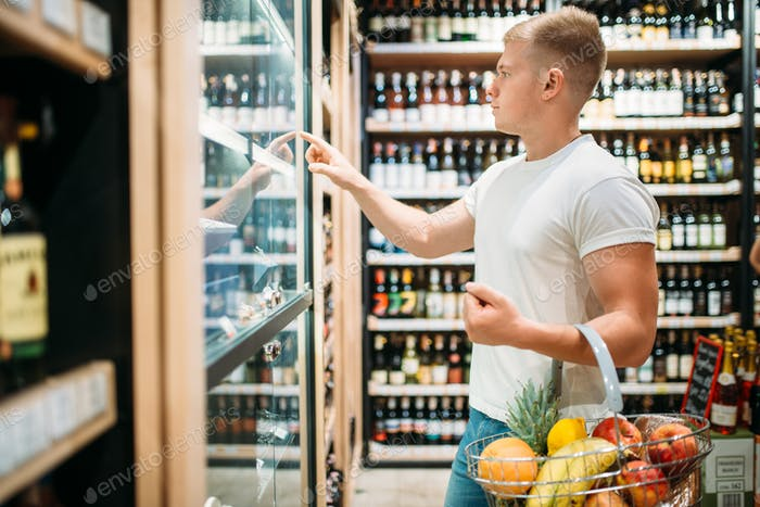 Customer with basket choosing beer in supermarket