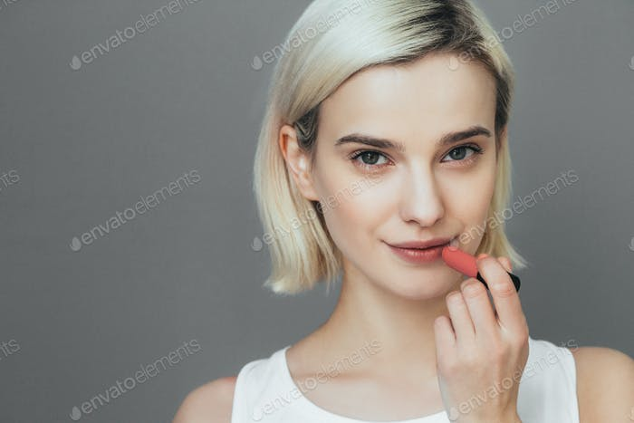 Woman lipstick makeup portrait. Beautiful female with red pink lips over gray wall