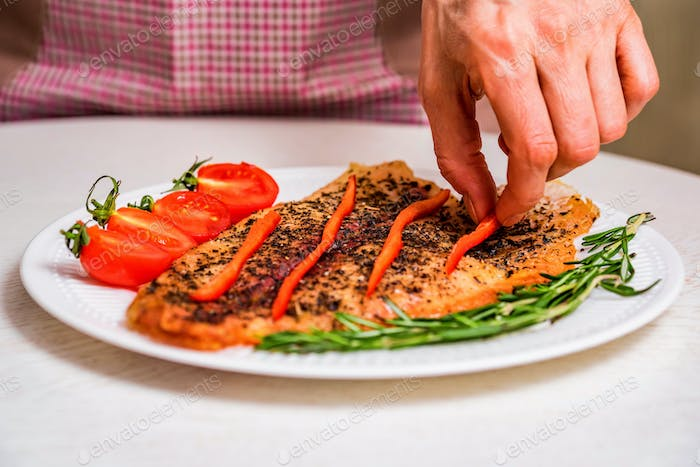 Cooking roasted fish fillet with vegetables close
