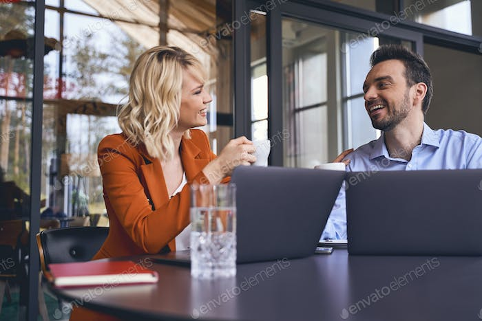 Stylish blonde young manager encouraging her coworker