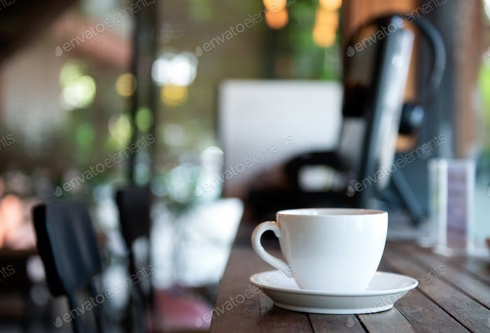 White coffee cup on wooden floor in cafe.