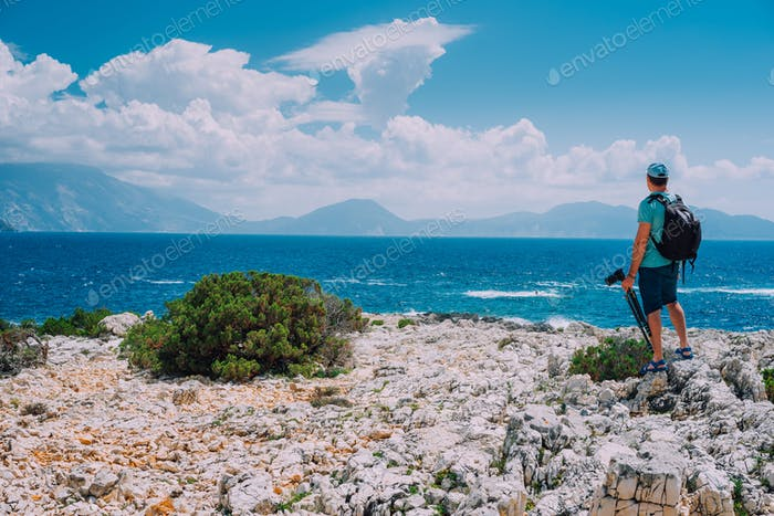 Male tourist with camera admiring breathtaking cloud scenery over the mountain range at the