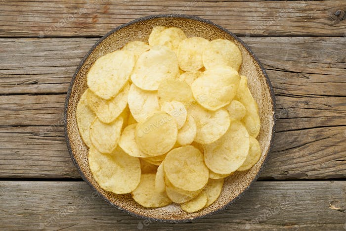 crisp in bowl, wooden background, top view