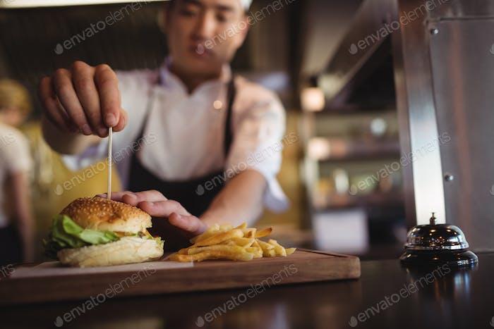 Chefkoch platziert Zahnstocher über Burger an der Bestellstation