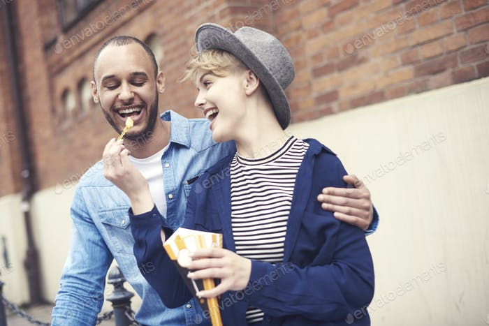 Young woman feeding boyfriend with French fries