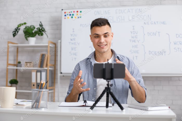 Attractive young man explains english rules and gestures on webcam in class