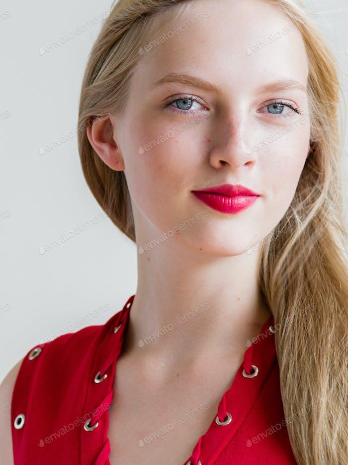 Nice woman in red dress blonde short hair. Fashion female portrait cute nice girl. Studio shot.
