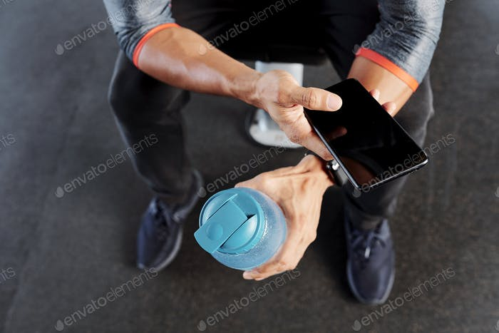 Active man with water bottle and smartphone