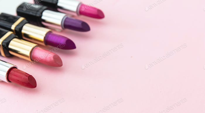 Lipsticks various colors against pink background, closeup view