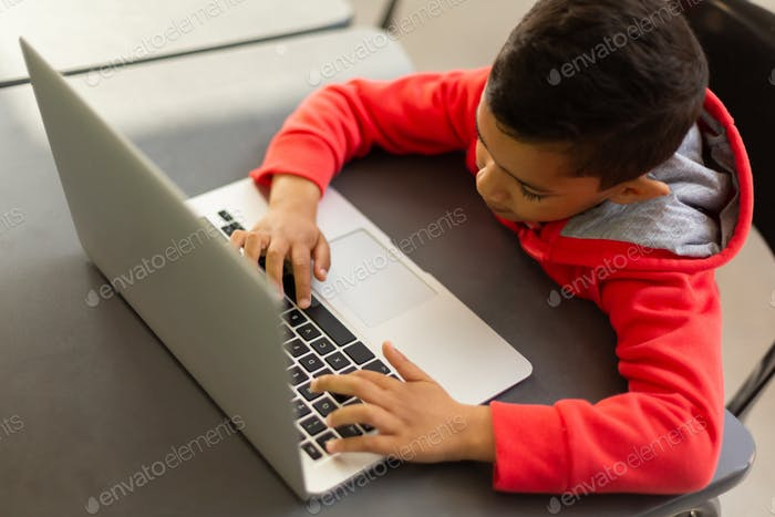 High angle view of mixed-race schoolboy using laptop at desk in a classroom at elementary school