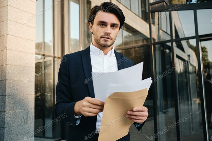 Young businessman thoughtfully looking in camera with documents in hands over glass building