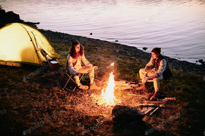 Young romantic couple sitting by fire on riverbank, talking and frying sausages