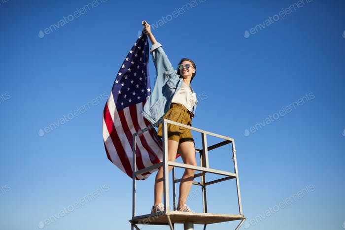 Modern girl putting up American flag on lifeguard place