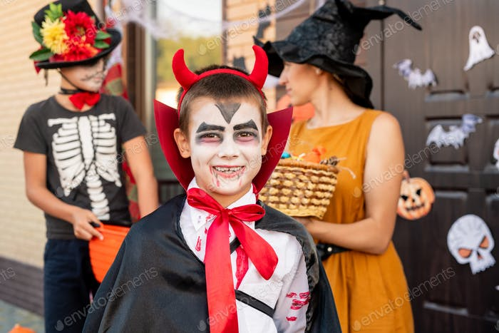 Cheerful boy in halloween costume looking at you against young woman and friend