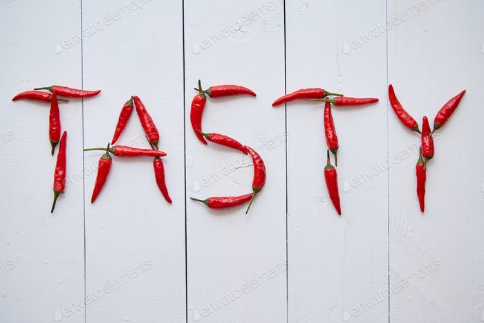 A word TASTY formed with small red chilli peppers. Placed on white wooden table