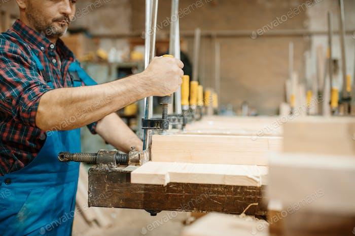 Zimmermann klemmt das Brett in einen Schraubstock, Holzbearbeitung