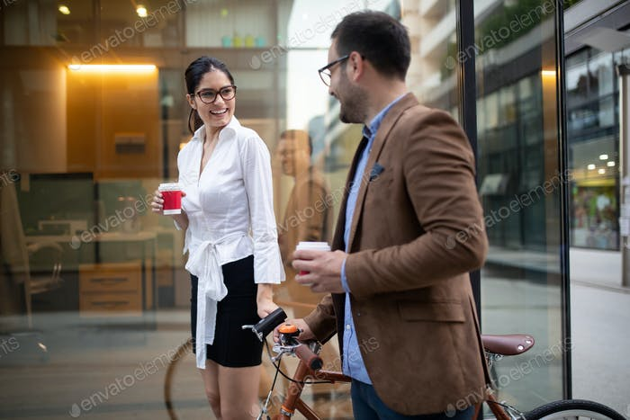 Couple of happy colleagues talking while walking in the street