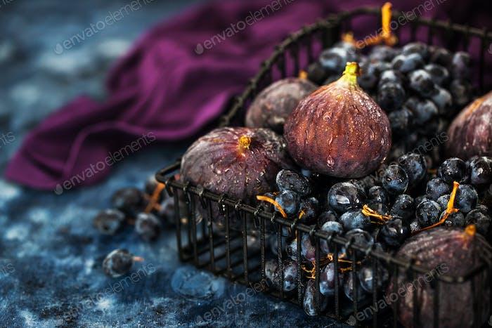 Higos frescos y uva morada en cesta