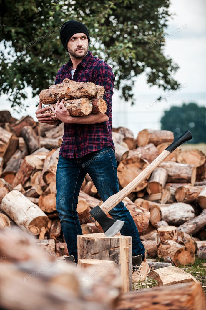 Lumberjack at work. Handsome young forester holding logs and looking away while standing outdoors