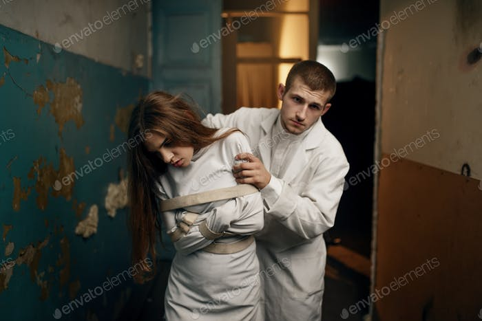 Psychiatrist leads female patient in straitjacket