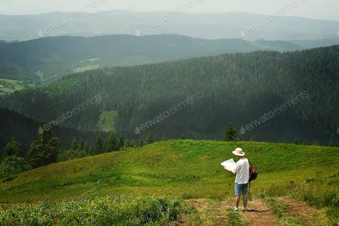 Traveler hält Karte und zu Fuß zum Gipfel des sonnigen Hügels auf dem Hintergrund der erstaunlichen Berge